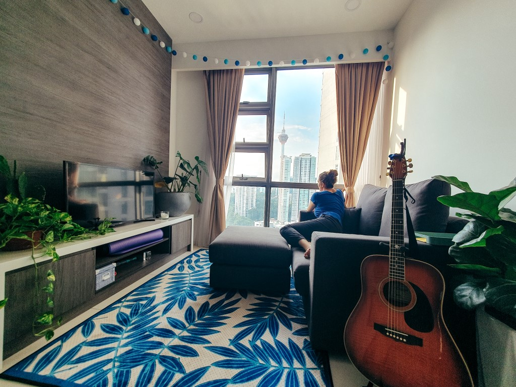 the living room of an apartment in a high rise building in Kuala Lumpur with a TV, coach, coffee table, guitar and a woman looking out the window at the view