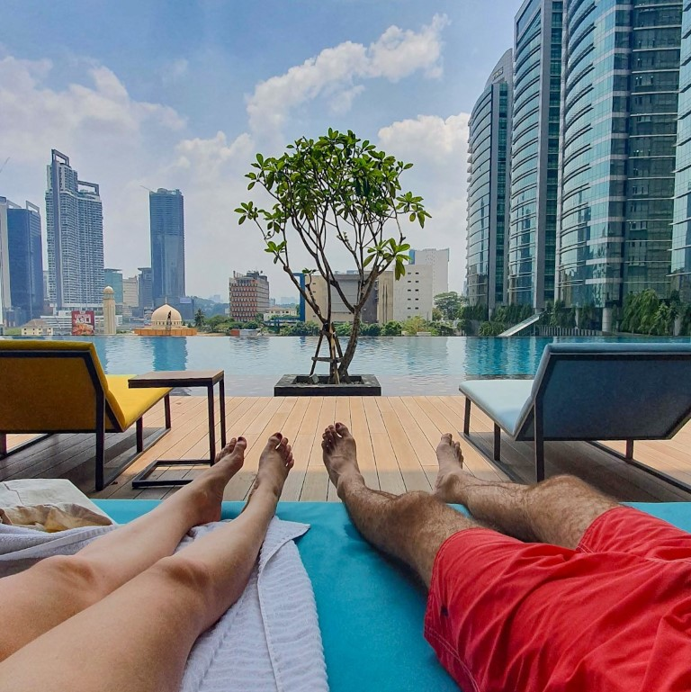 two people sitting next to an infinity pool in kuala lumpur with the city in the background