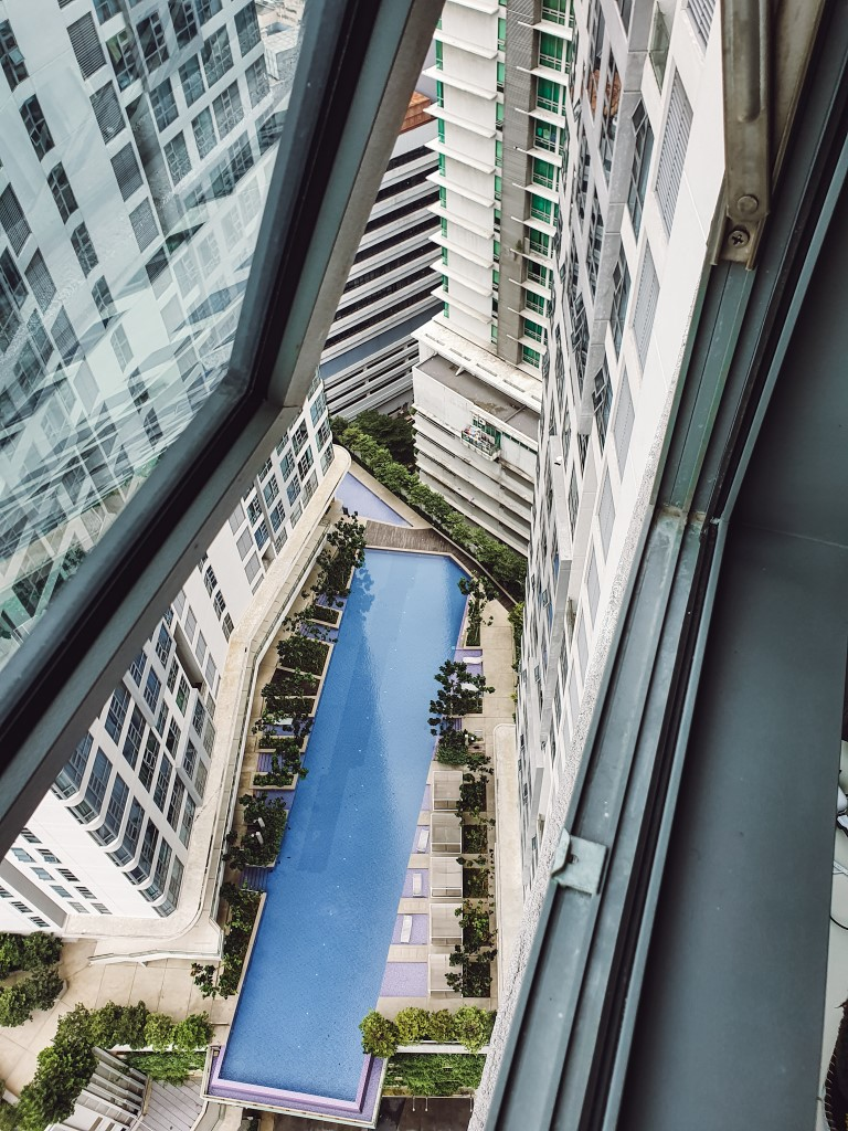 a view out of a side window of a high rise to the swimming pool nearly 20 floors below