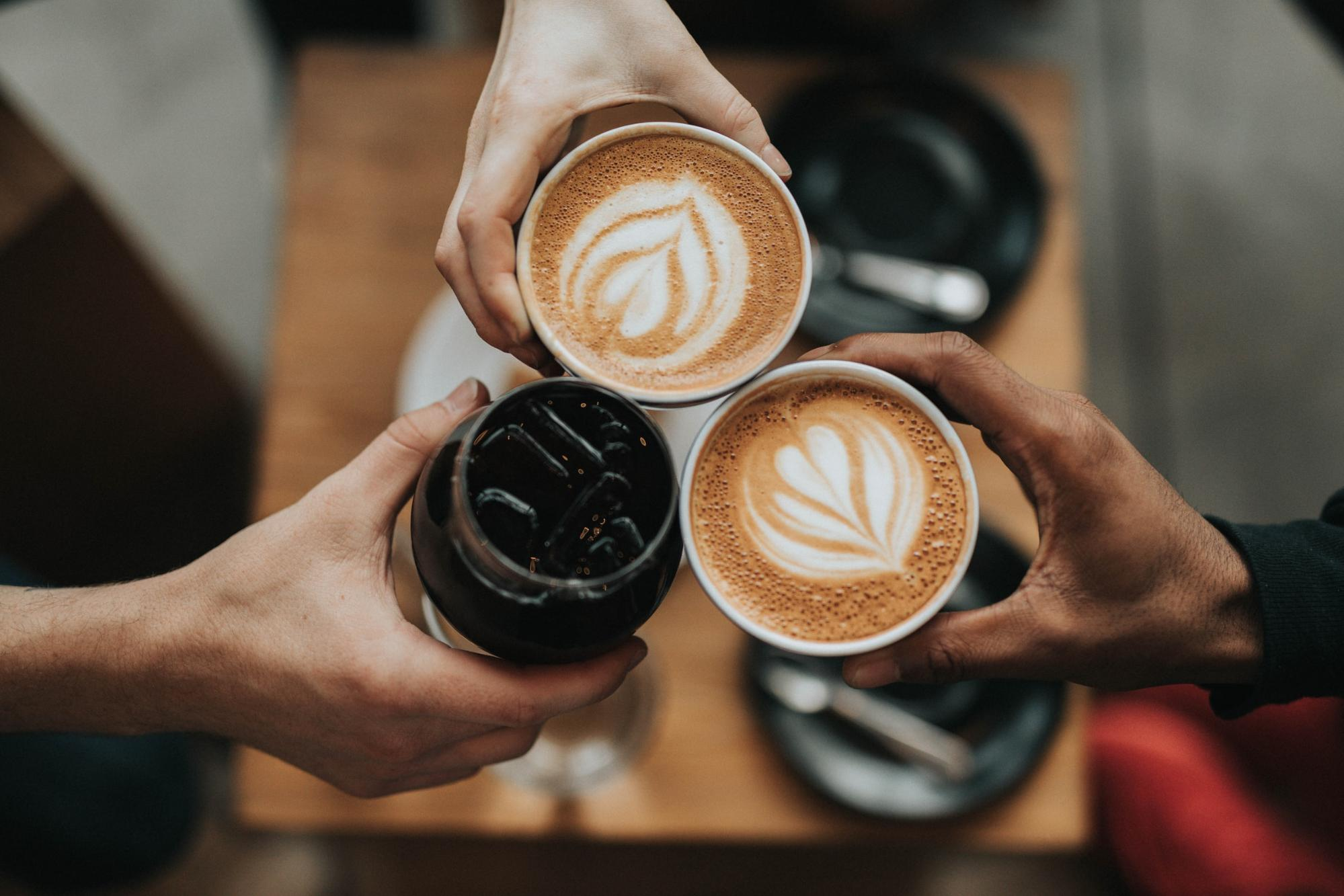 An overhead view of three people cheersing their coffees at a coffee shop