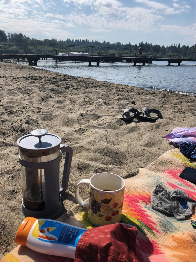 A picnic in the sand off the coast of Seattle with a french press coffee, towel, and sunscreen