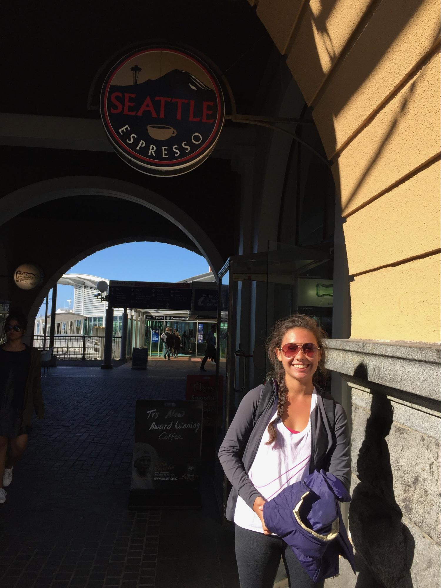 """A woman posing in front of the """"Seattle Espresso"""" coffee shop in Auckland, NZ."""