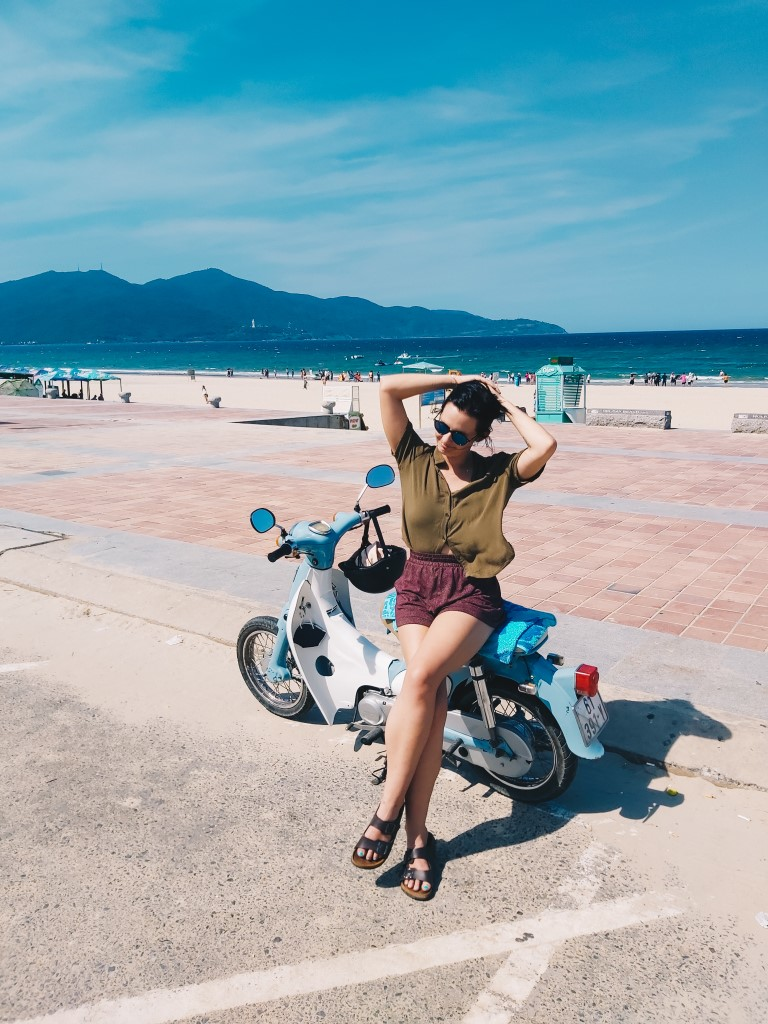 A woman sitting on her parked Honda Cub in front of a beach backdrop in Vietnam