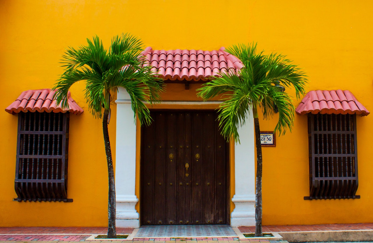 A bright yellow house with 2 palm trees beside the door and red tile awnings over the door and windowss