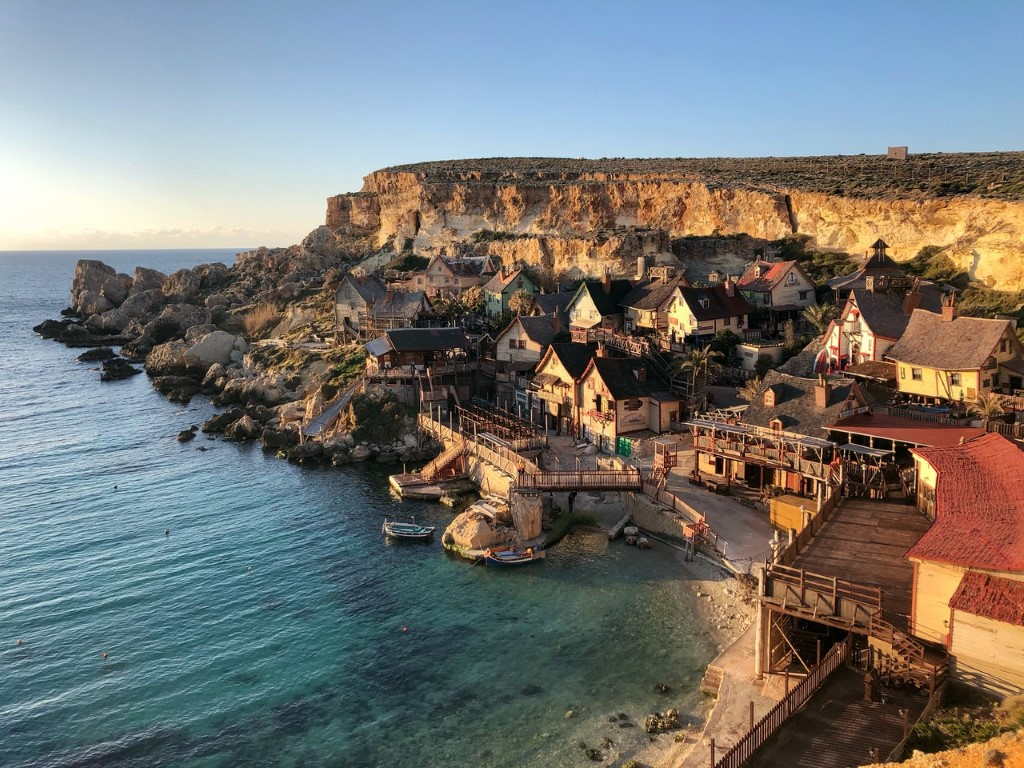 a view of the Maltese coastline withrocks and old wooden houses