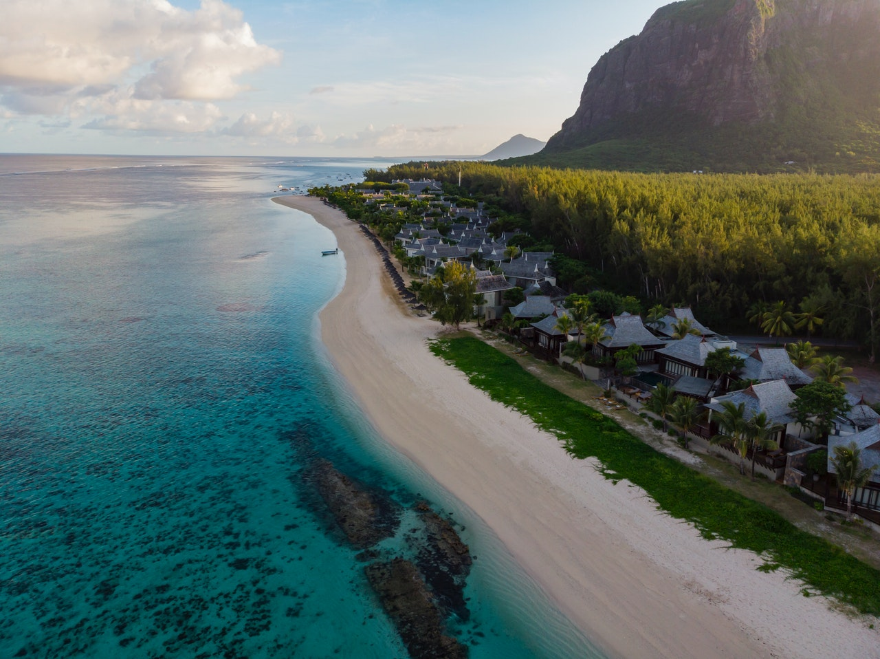 Mauritius coasline with mountains, houses, and trees along the beach