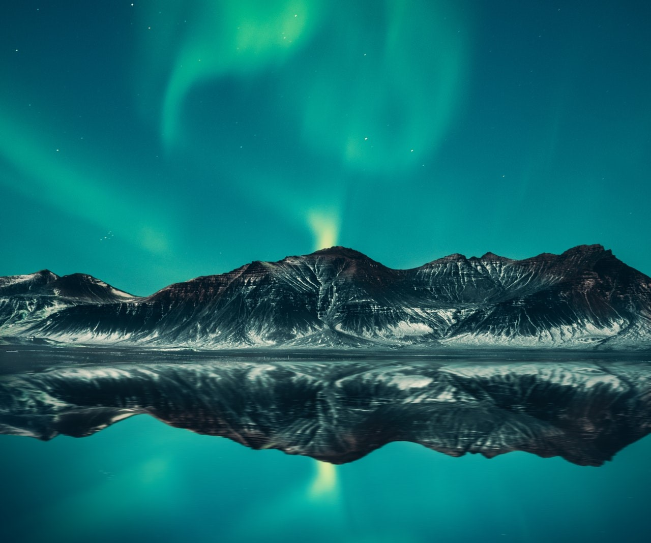 blue and green northern lights really visible over the mountains and a lake in Iceland