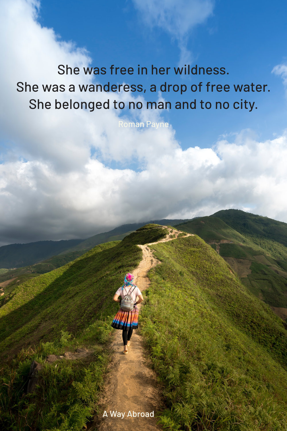 a woman in a bright skirt walking down a trail at the top of a hill