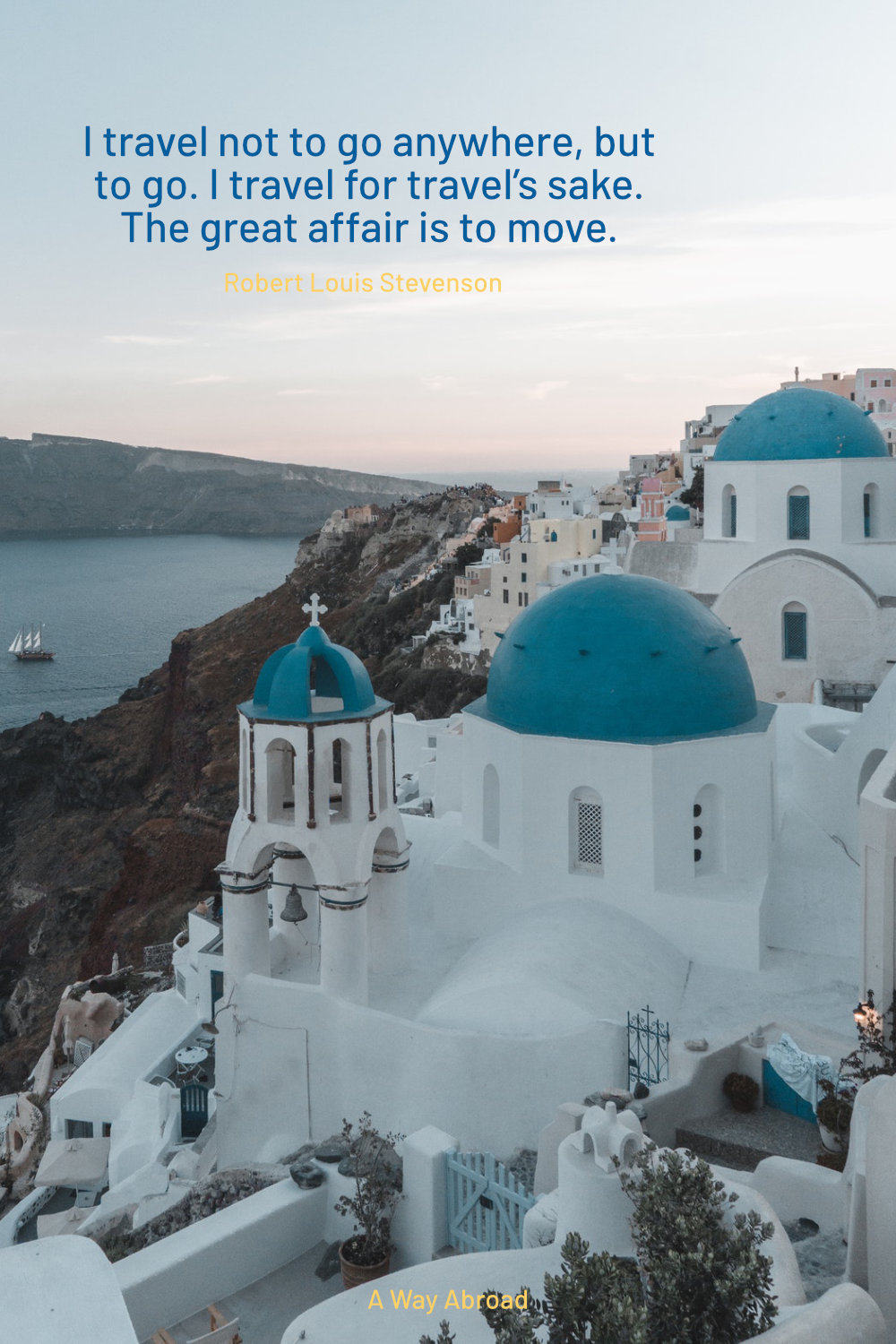 Santorini at sunset with the white and blue buildings overlooking the sea and mountains
