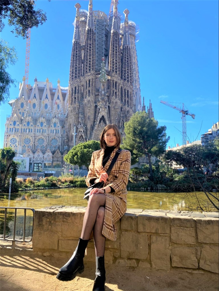 a woman sitting in front of the Cathedral in Barcelona
