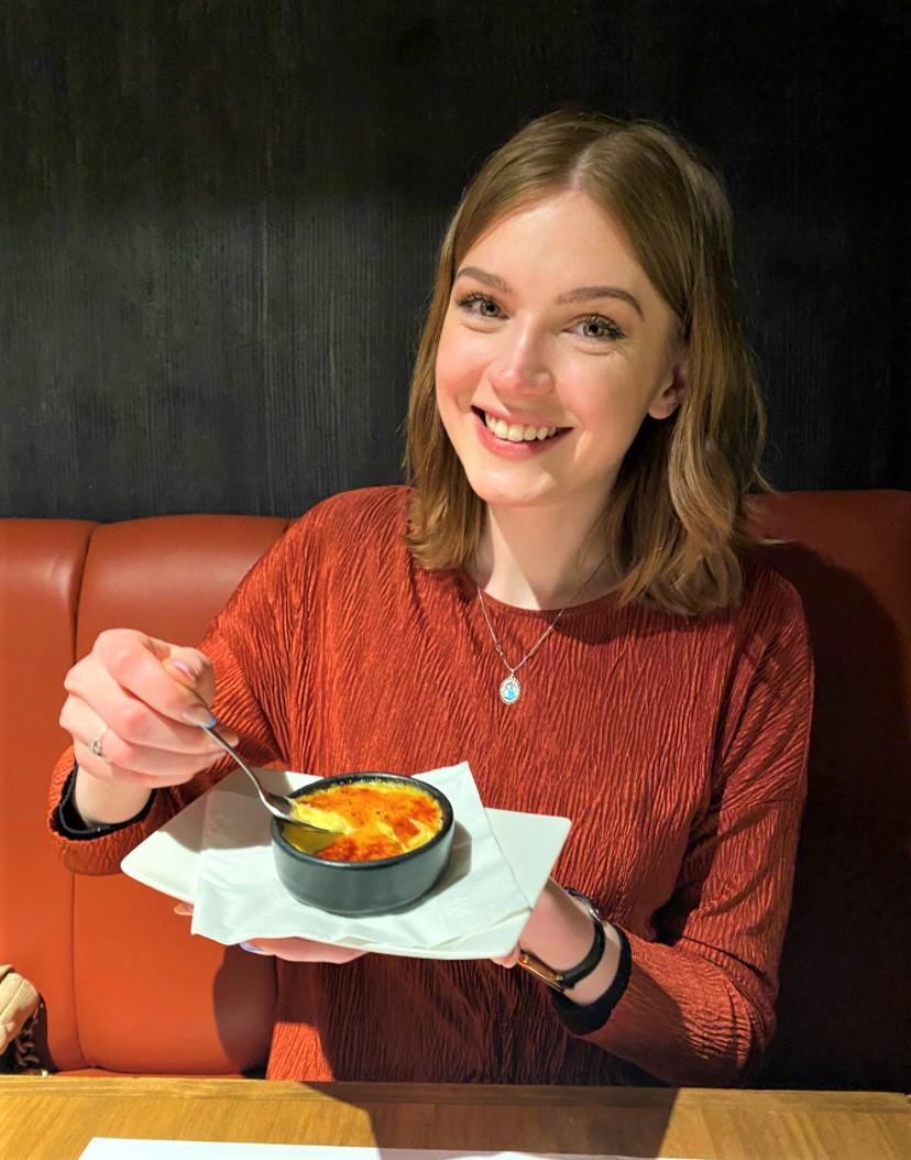 a woman eating a crema catalana and smiling at the camera