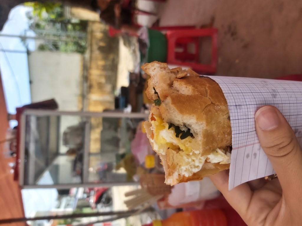 a bite taken out of a banh mi op la, vietnam's egg sandwich