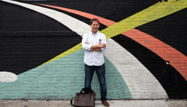 Wright Harvey of Sugarlift standing in front of a blue, black, orange, and yellow mural