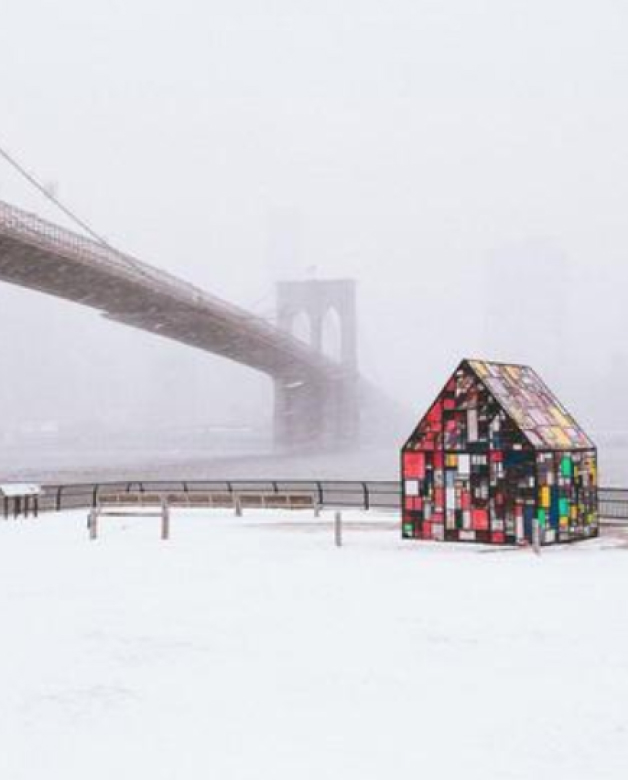 Fine art photography by Humza Deas of a little red house and a long bridge in a snowstorm