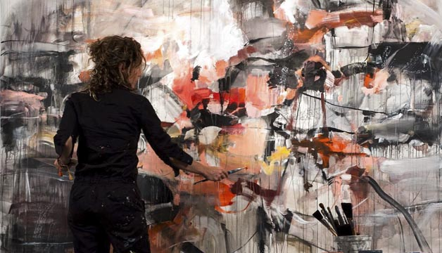 artist looking up at large original painting in a studio