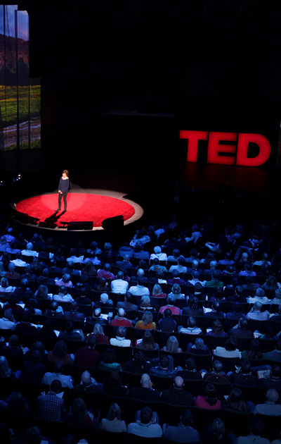 Speaker on stage at a TED event with a large audience