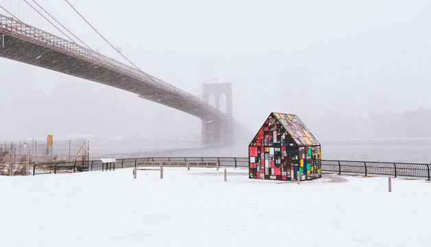 Humza Deas photography of a colorful house and a long bridge under the snow