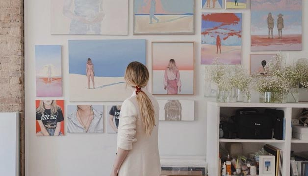 Woman turned towards a gallery wall of Helen Robinson's paintings