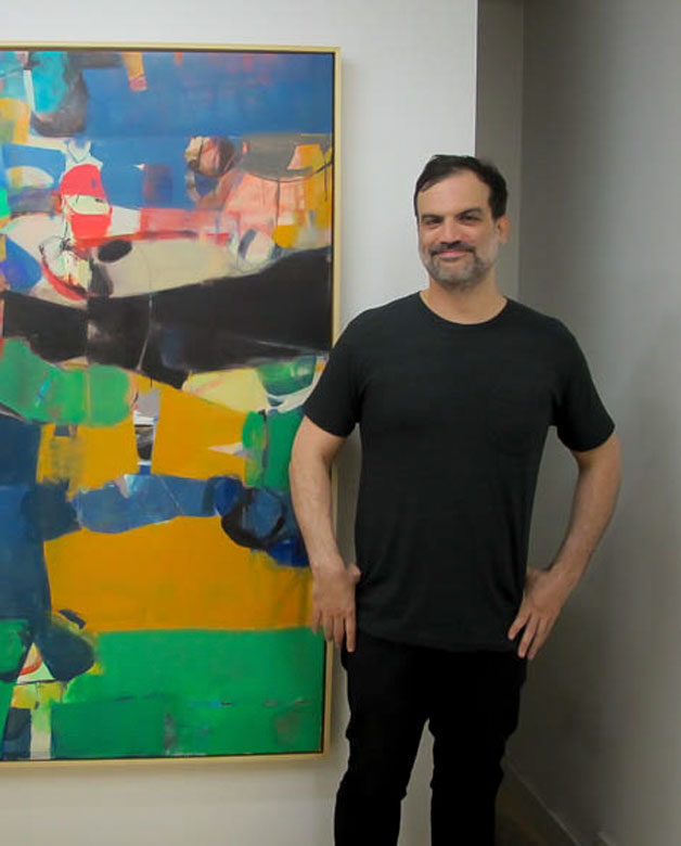 Robert Szot standing in front of one of his paintings