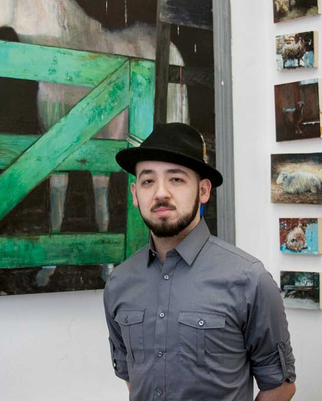 Nicolas V. Sanchez in front of his paintings