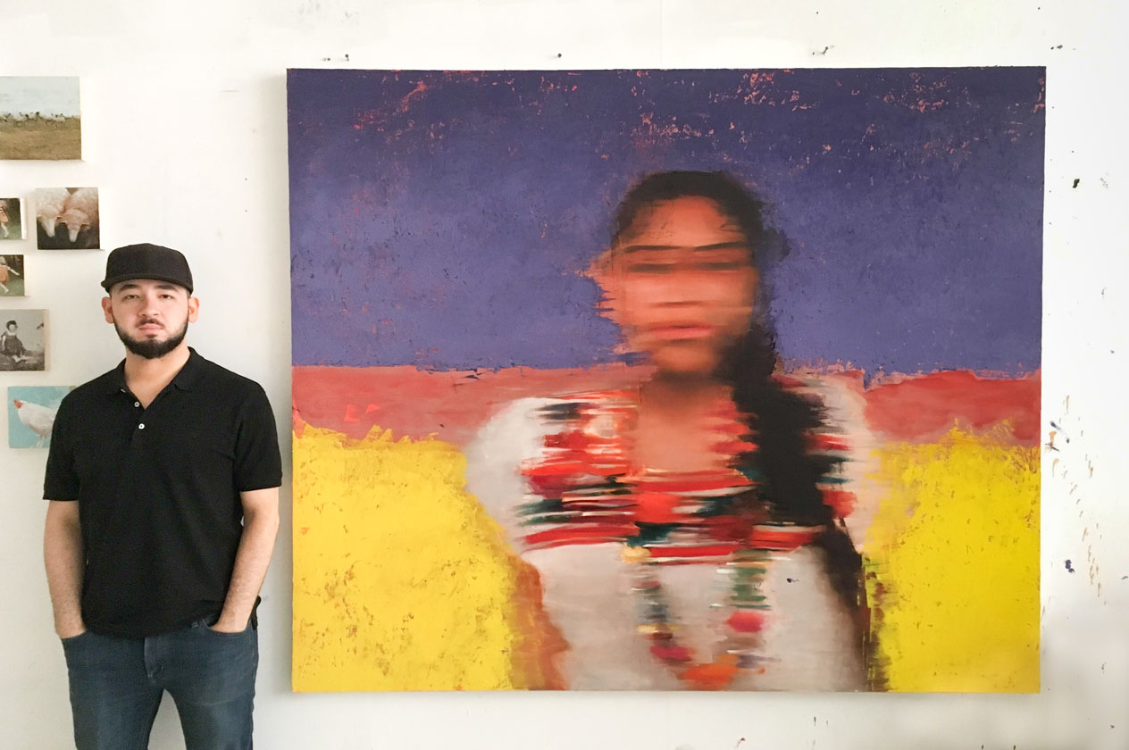 Nicolas V. Sanchez in front of his colorful large-scale painting of a blurred woman