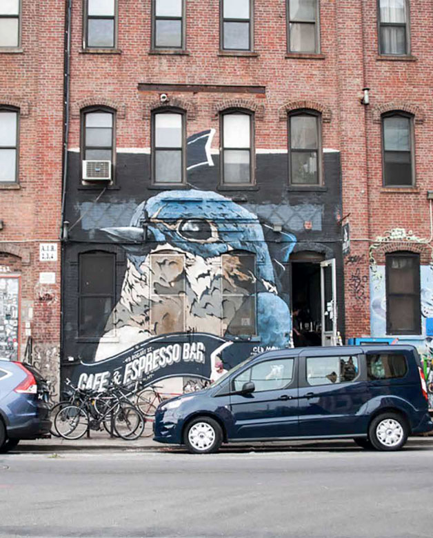 Large mural of a blue bird on a brick storefront by Morgan Studio in Brooklyn