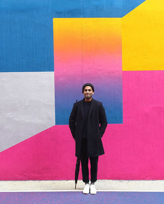 Karan Singh standing in front of his bright pink, blue, and yellow mural