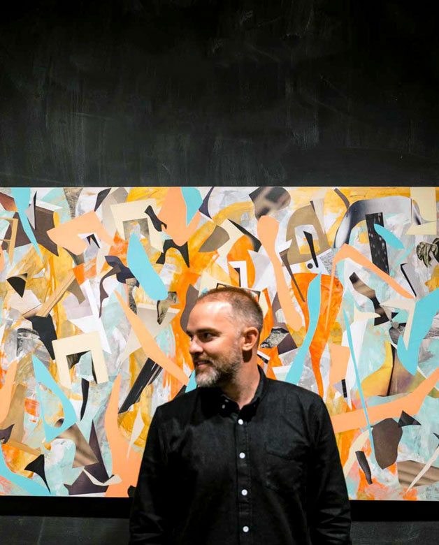 Jon Legere in front of an orange and blue abstract painting