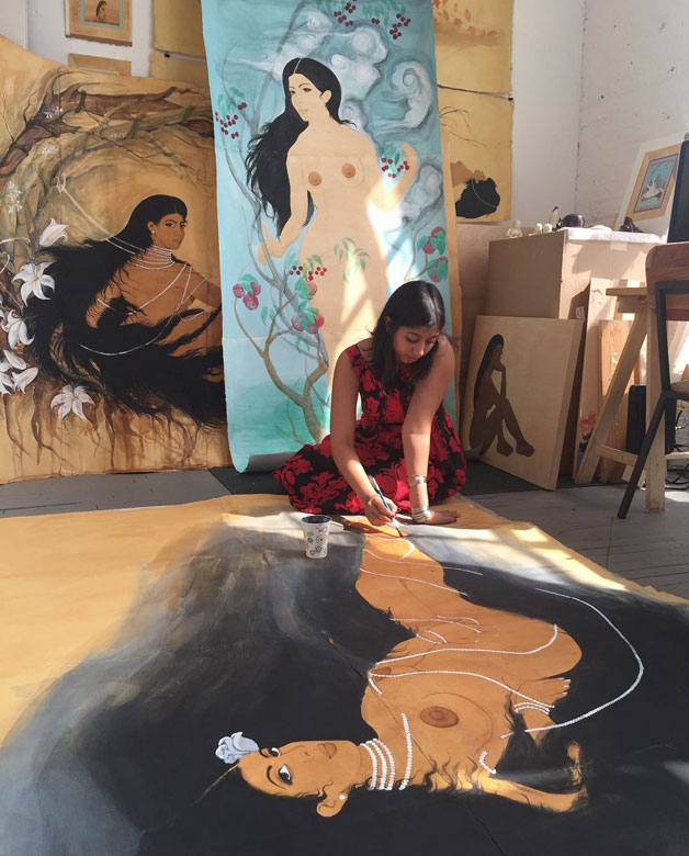 Hiba Schahbaz on the floor of her studio working on a painting