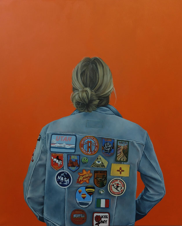 Portrait of a woman in a jean jacket with patches and an orange background by Helen Robinson