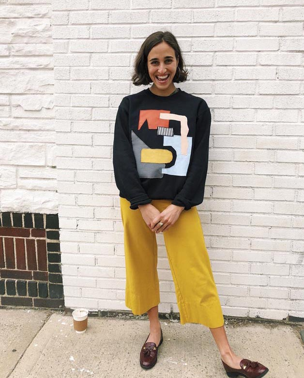 Kristin Teixeira in yellow pants in front of a white brick wall