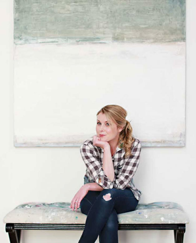 Kiki Slaughter sitting in front of one of her large paintings