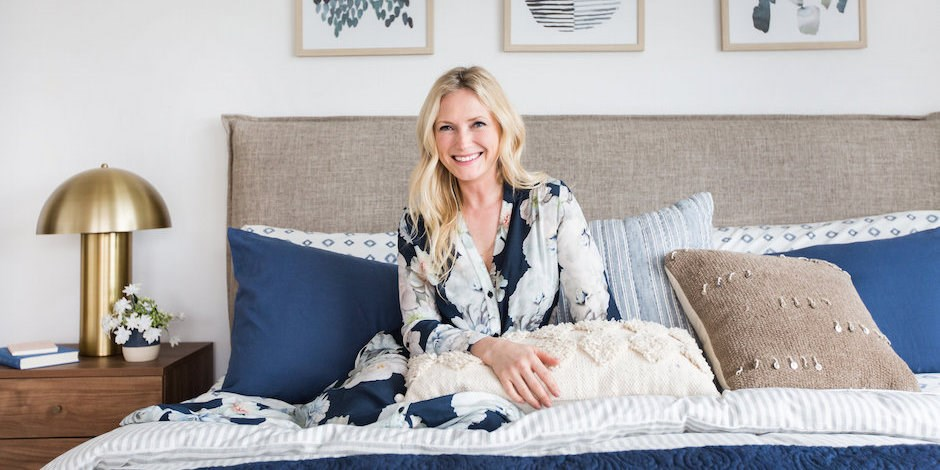 Emily Henderson the interior designer, sitting on a bed after having written an article about Sugarlift's prints and original art