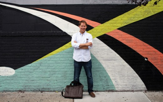 Founder of Sugarlift Wright Harvey standing in front of a mural in New York