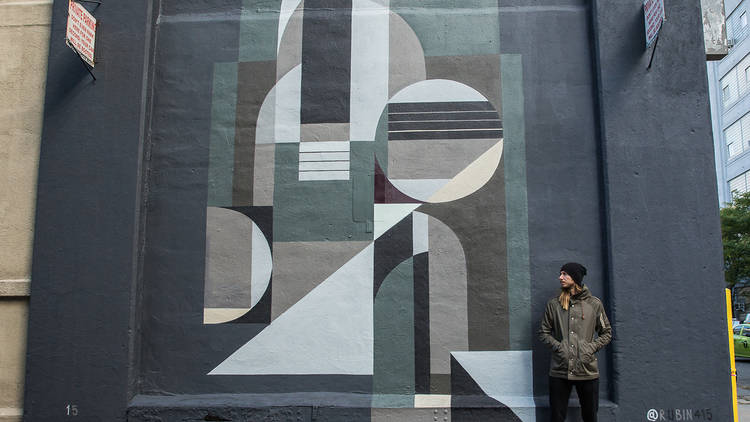 Sugarlift artist Rubin415 in front of one of his murals in New York