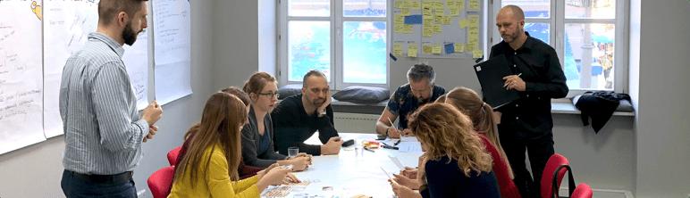 Zdjęcie uczestników szkolenia pracujących przy stole.
