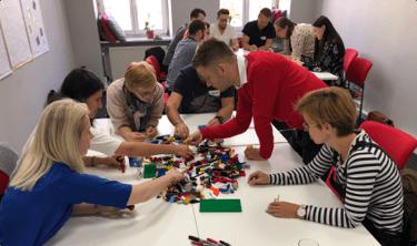 Zdjęcie uczestników szkolenia budujących z klocków LEGO.