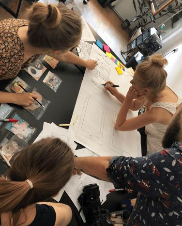 Zdjęcie uczestniczek warsztatów pracujących nad papierowym prototypem