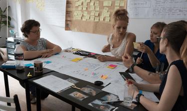 Zdjęcie grupy uczestników i trenerki pracujących nad papierowym prototypem