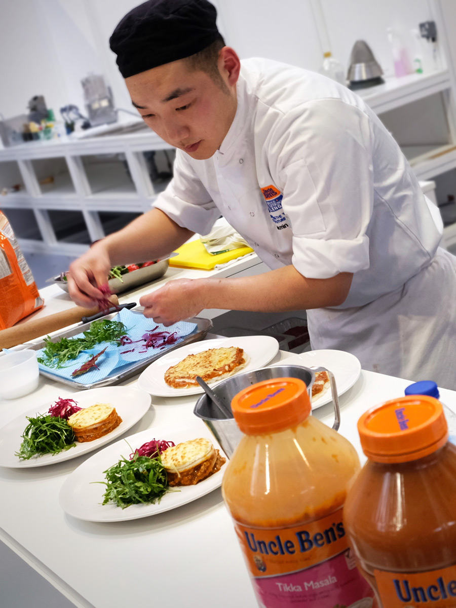 A young chef busily preparing a meal during a cooking competition.
