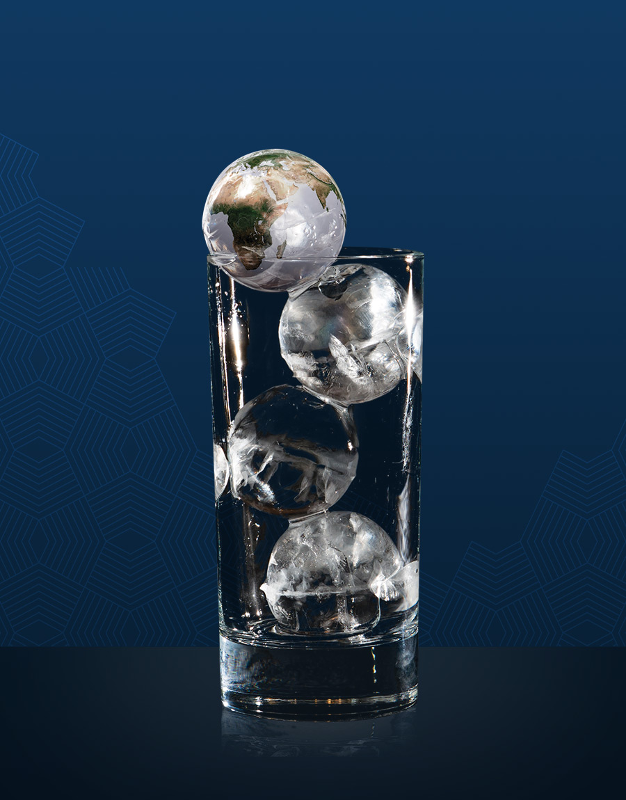 A glass of circular ice cubes against a deep blue background. One of the ice cubes has a photo of the earth laid on top.