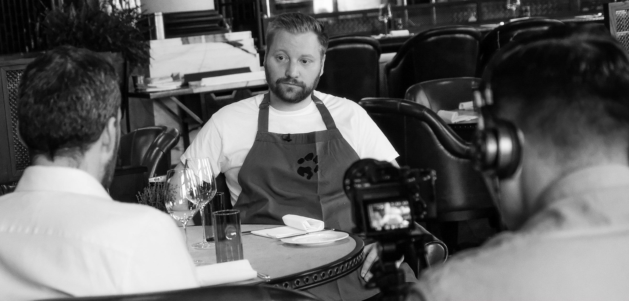 A chef being interviewed in a restaurant as a videographer records him.