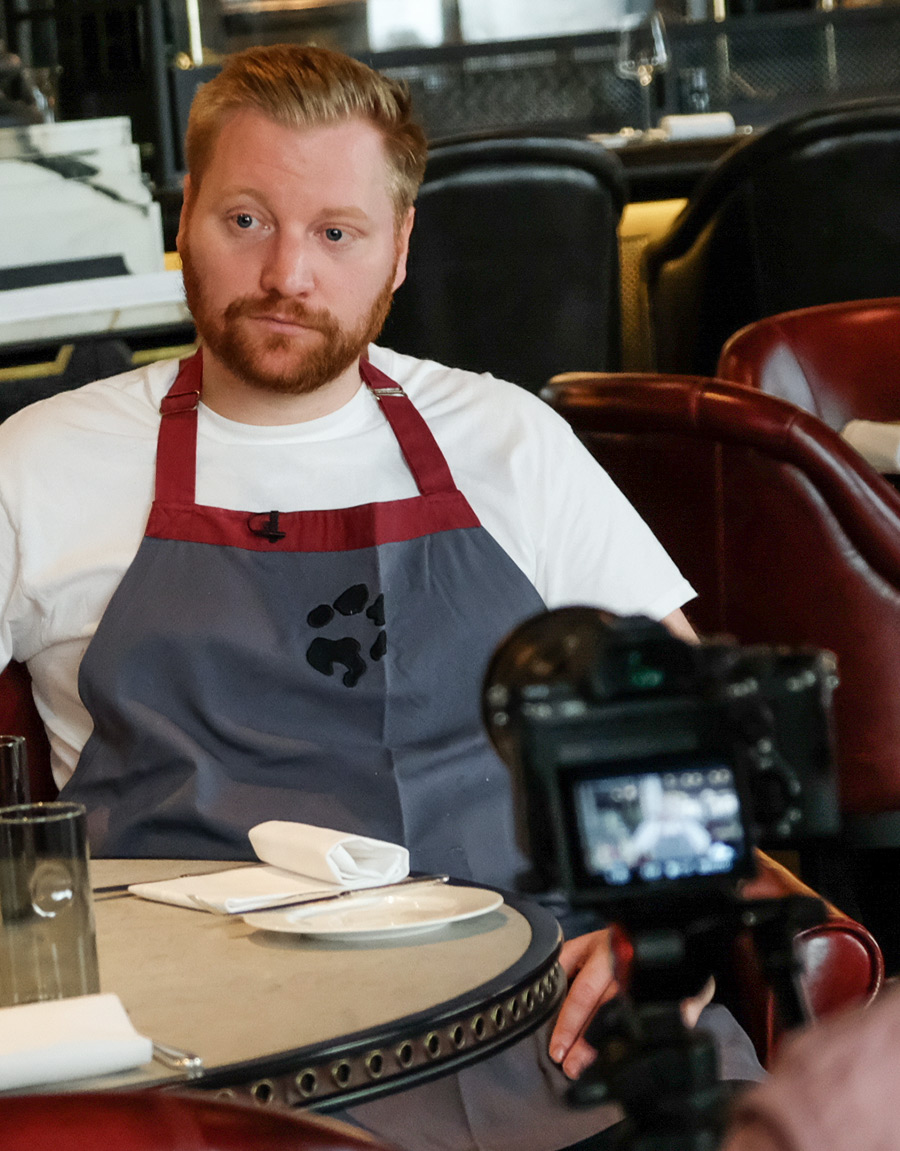 A chef sat in a restaurant being interviewed as a camera records him.