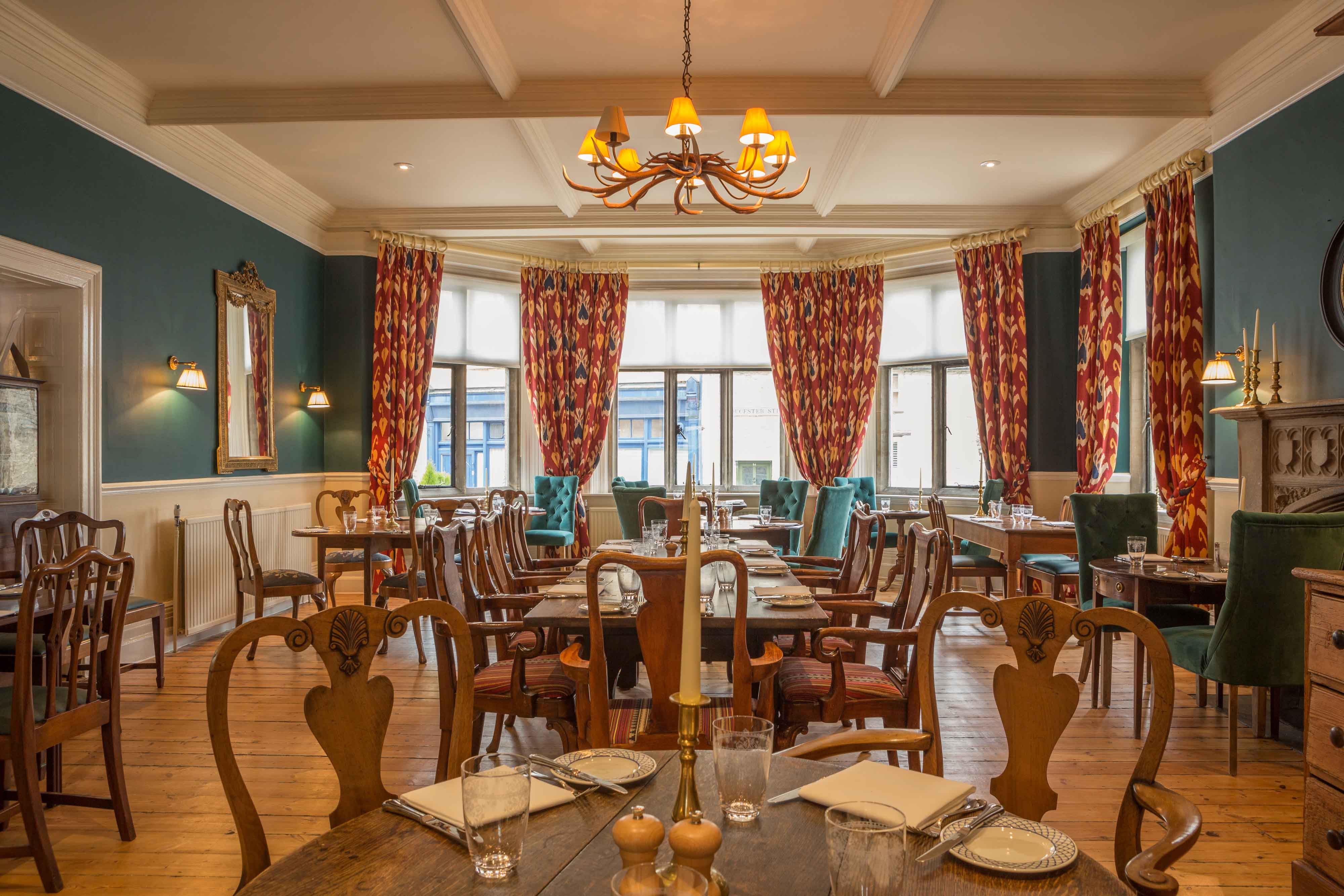 The luxurious interior of the hotel's dining room with blue walls and elegant furnishings.