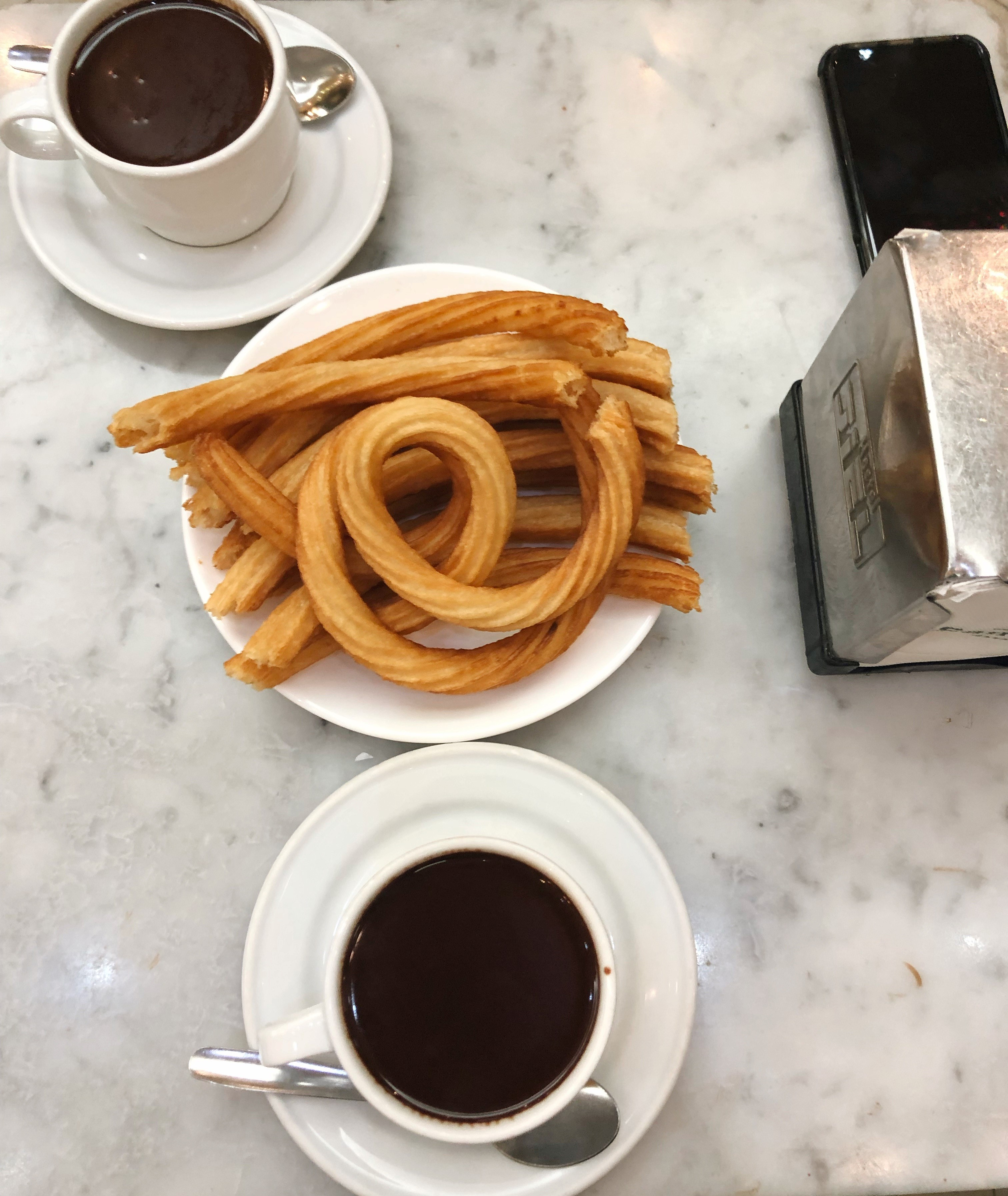 A plate of churros and two black coffees.