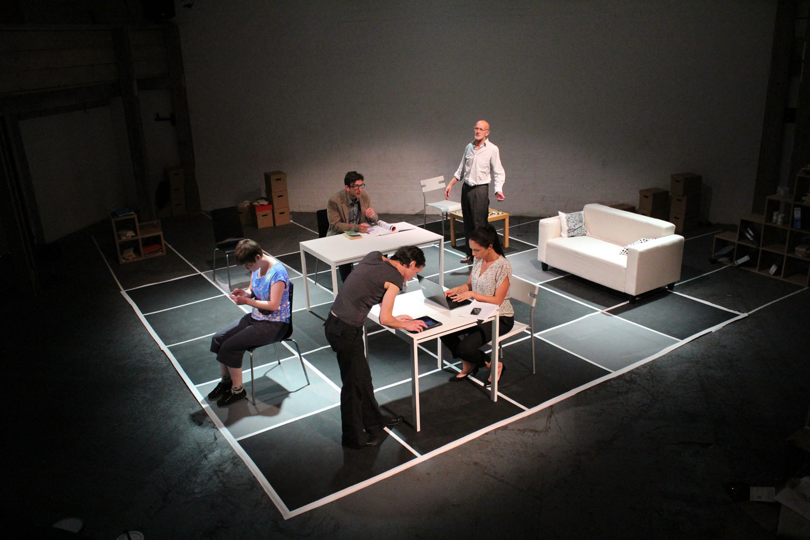 There is a huge huge black and white chessboard with tables, chairs and a sofa positioned on different squares. Five characters sit or stand at different angles engrossed in their work