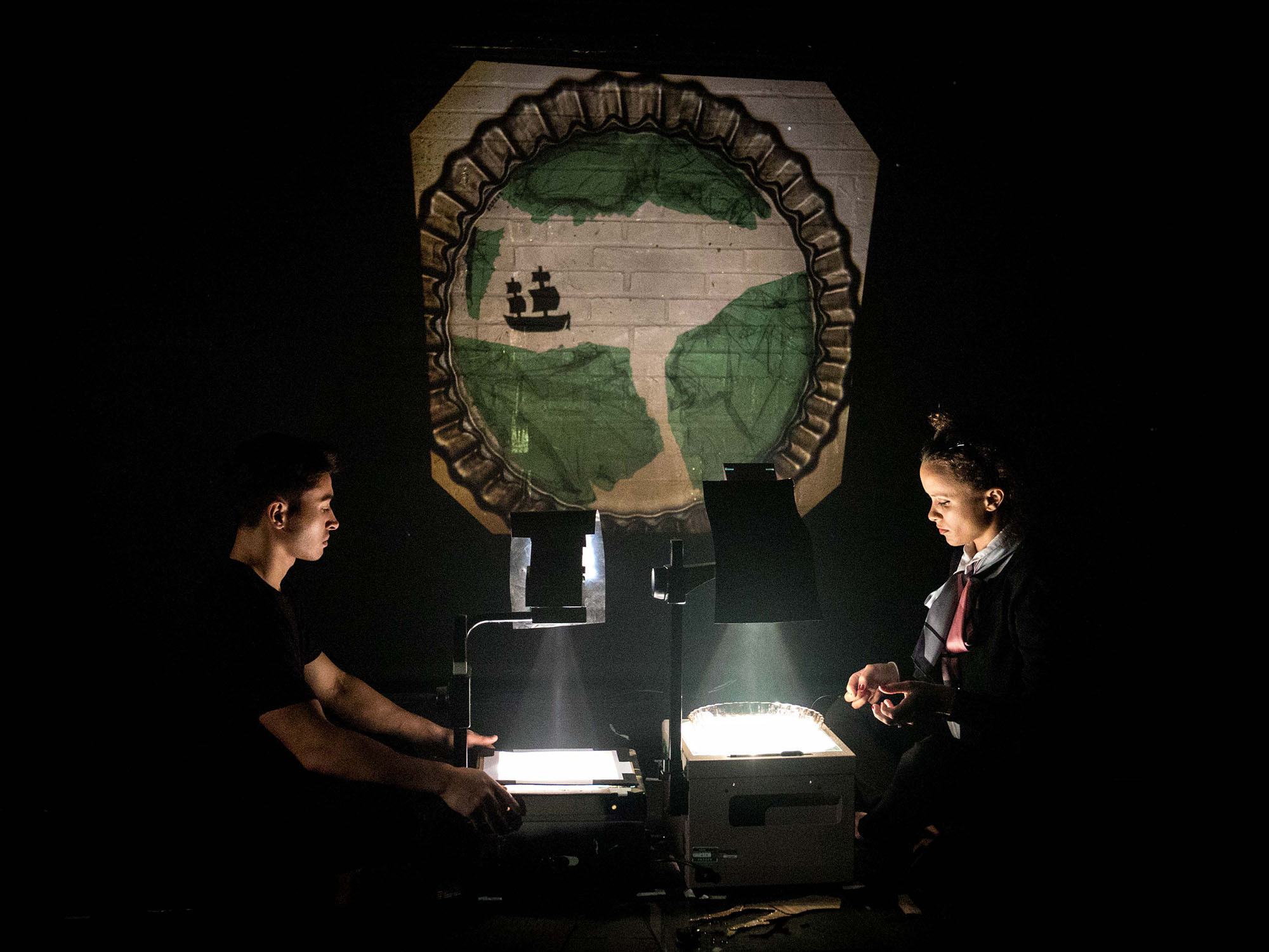 Two performers dressed in black crouch in the dark by two overhead projectors. These project a handmade image of a map of land and ocean with a ship sailing on it