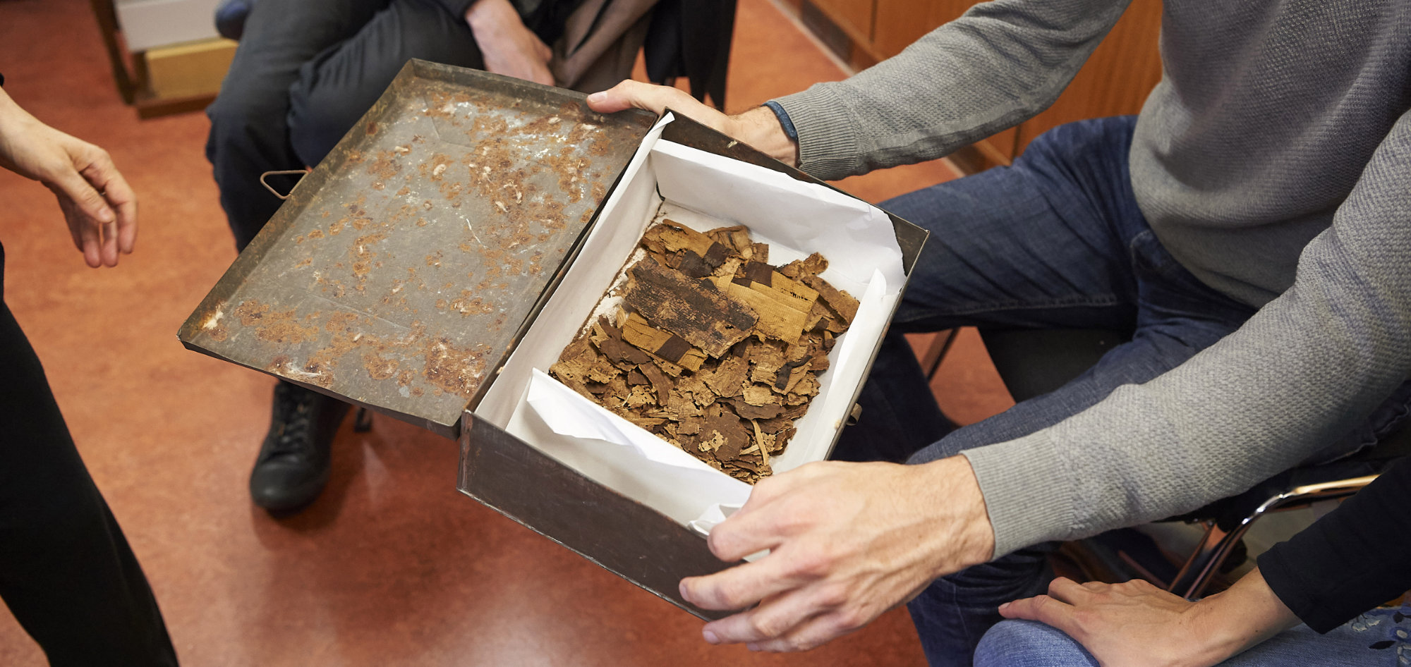 An old tin box being held open containing dozens of fragments crumpled papyrus