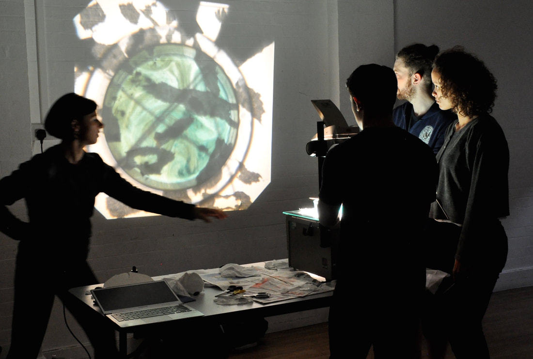 Performers in dark clothes crowd around an overhead projector at a desk looking an image it is projecting of colours and shapes