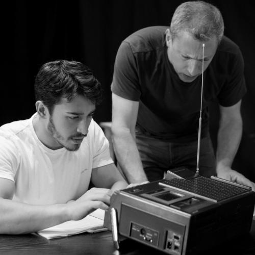 In black and white: a young man with dark hair, a trendy beard and wearing a white t-shirt sits at a table fiddling with knobs on some sort of old-fashioned radio. Next to him, an older man, in a dark t-shirt is leaning forward peering at the same radio looking confused. Around them float colourful logos for tech companies and platforms.